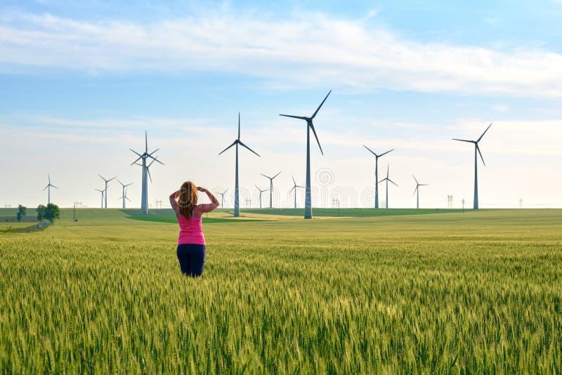 Mulher e turbinas eólicas no por do sol, em um campo do centeio verde, com luz morna do sol Conceito para a energia sustentável,  foto de stock