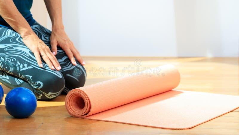 Mulher e uma esteira da ioga no assoalho de madeira foto de stock