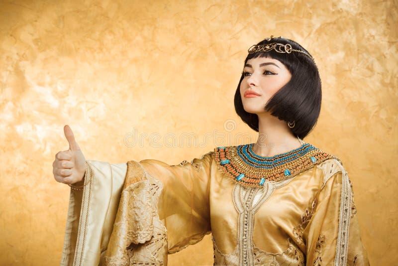 A mulher egípcia de sorriso feliz gosta de Cleopatra com os polegares acima do gesto, no fundo dourado fotos de stock