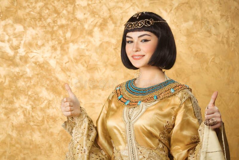 A mulher egípcia de sorriso feliz gosta de Cleopatra com os polegares acima do gesto, no fundo dourado imagem de stock royalty free