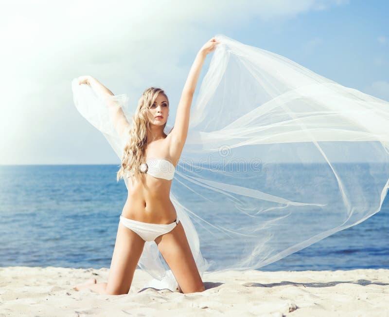 Mulher elegante, atrativa no roupa de banho de fascínio que levanta no bea imagens de stock royalty free