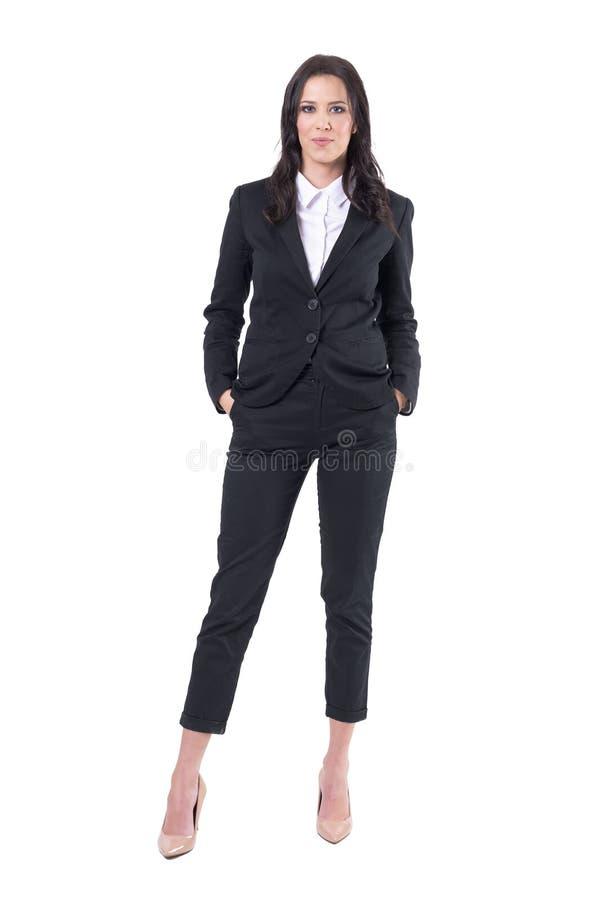 Mulher elegante atrativa no terno de negócio preto que levanta com mãos em uns bolsos foto de stock royalty free