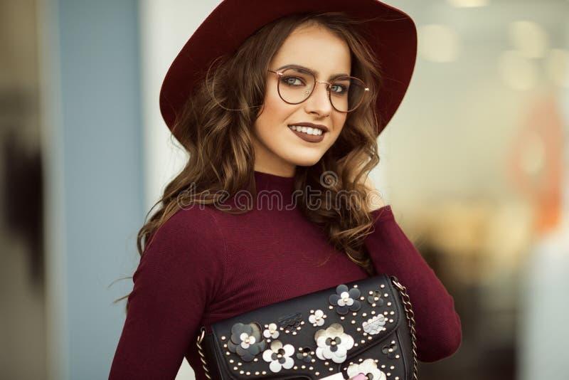 A mulher elegante bonita está vestindo a roupa e os vidros do outono da forma com saco preto, conceito da queda imagem de stock