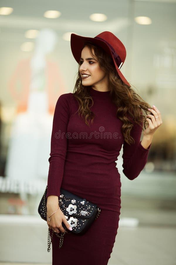 A mulher elegante bonita está vestindo a roupa vermelha do outono da forma com o saco preto na frente da loja-janela foto de stock royalty free