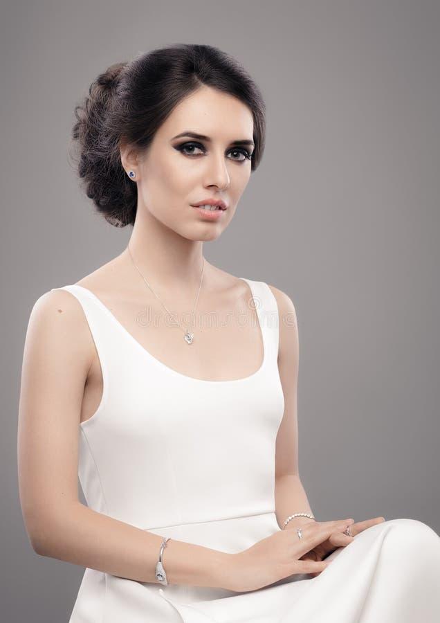 Mulher elegante bonita na joia vestindo do vestido branco imagens de stock royalty free