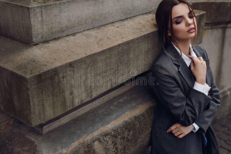 Mulher elegante bonita na roupa da forma que levanta na rua imagem de stock