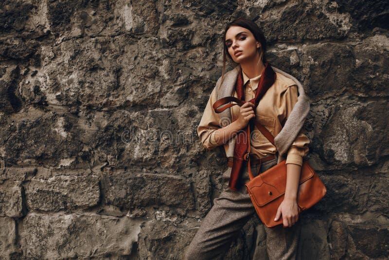 Mulher elegante bonita na roupa de forma que levanta perto da parede fotos de stock
