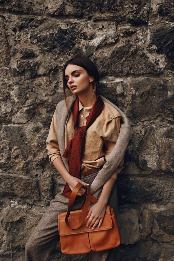 Mulher elegante bonita na roupa de forma que levanta perto da parede foto de stock