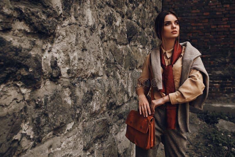 Mulher elegante bonita na roupa de forma que levanta perto da parede imagem de stock royalty free