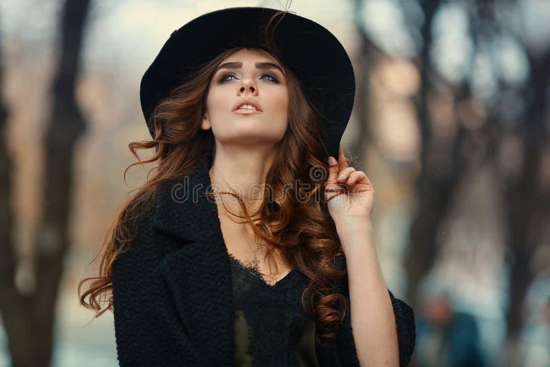 Mulher elegante bonita no chapéu negro exterior Olhar da forma, euro- foto de stock