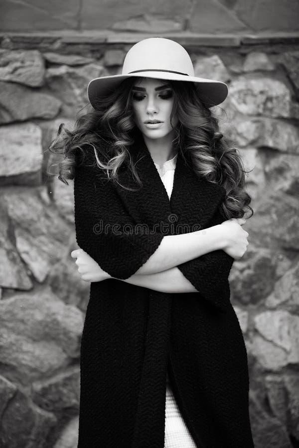 Mulher elegante bonita no ove preto na moda à moda do revestimento e do chapéu fotografia de stock