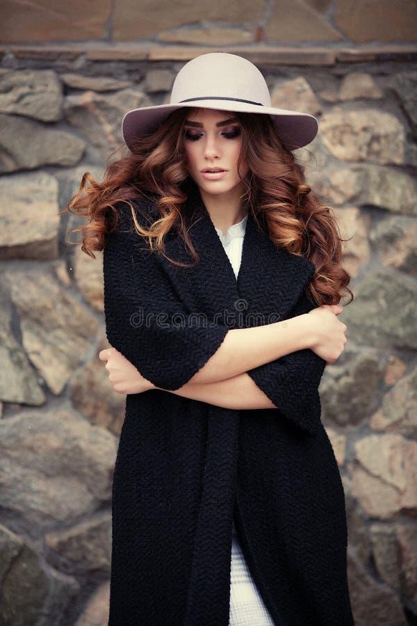 Mulher elegante bonita no ove preto na moda à moda do revestimento e do chapéu fotos de stock