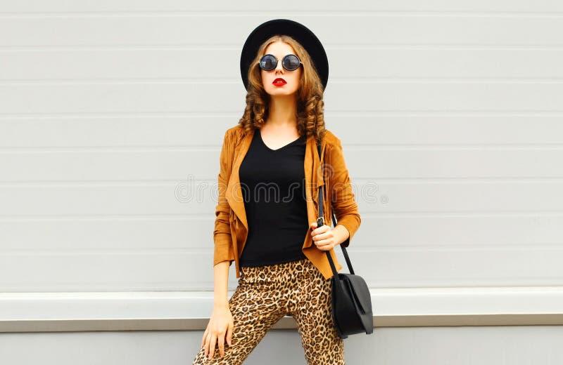 Mulher elegante bonita que veste um chapéu elegante retro, uns óculos de sol, um revestimento marrom e uma bolsa preta foto de stock royalty free
