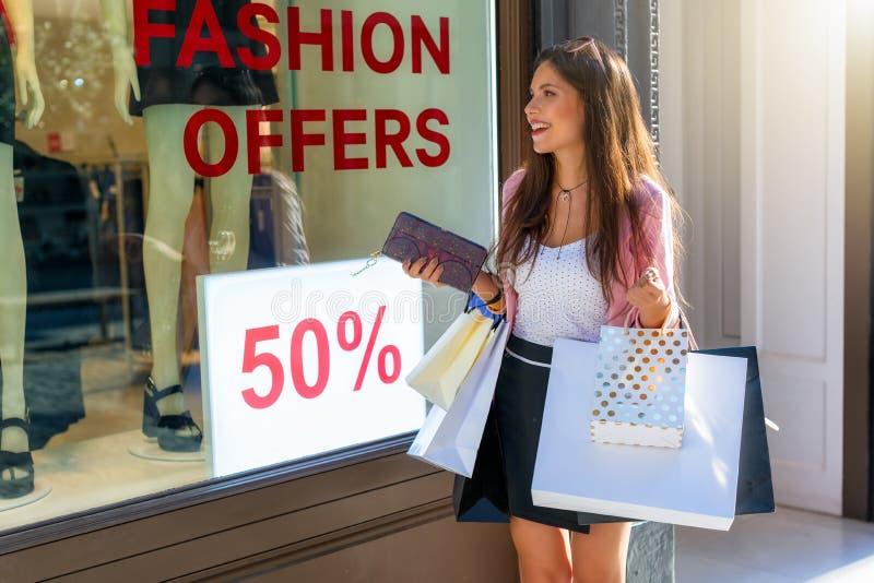 A mulher elegante da compra da cidade fica animado por vendas da forma fotos de stock royalty free