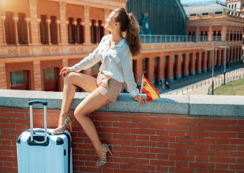 Mulher elegante de sorriso com a bandeira da Espanha que senta-se no parapeito fotografia de stock royalty free