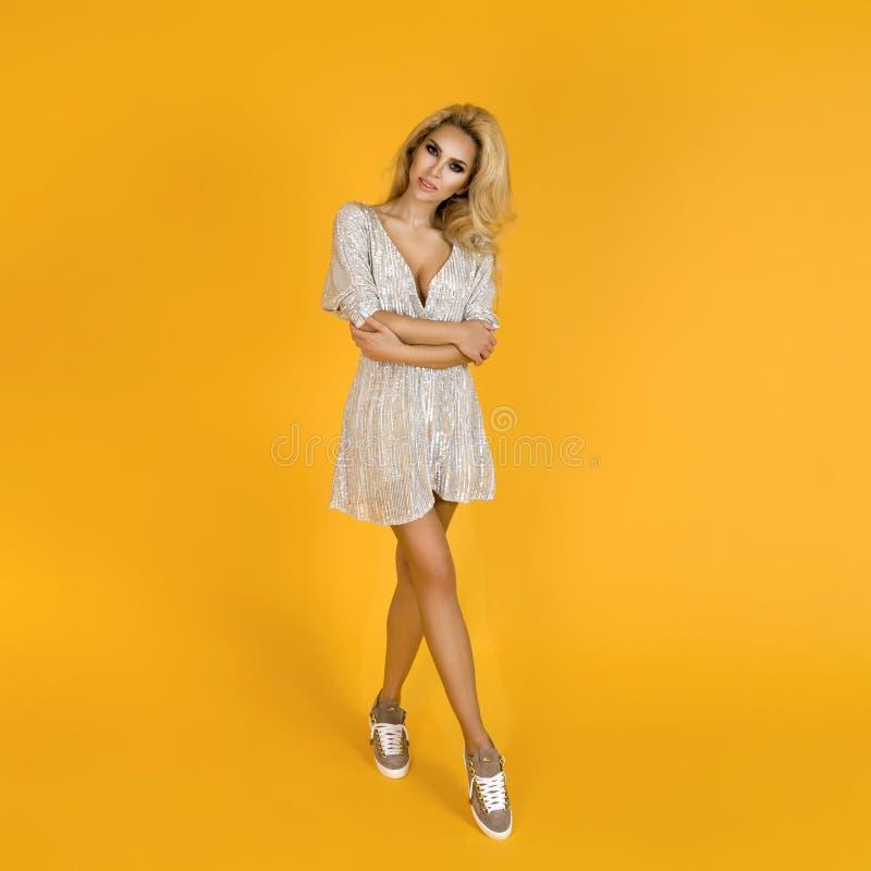 Mulher elegante em lantejoulas na moda mini vestido, sapatas e acessórios Foto do ver?o da mola da forma Moça feliz em um amarelo imagem de stock