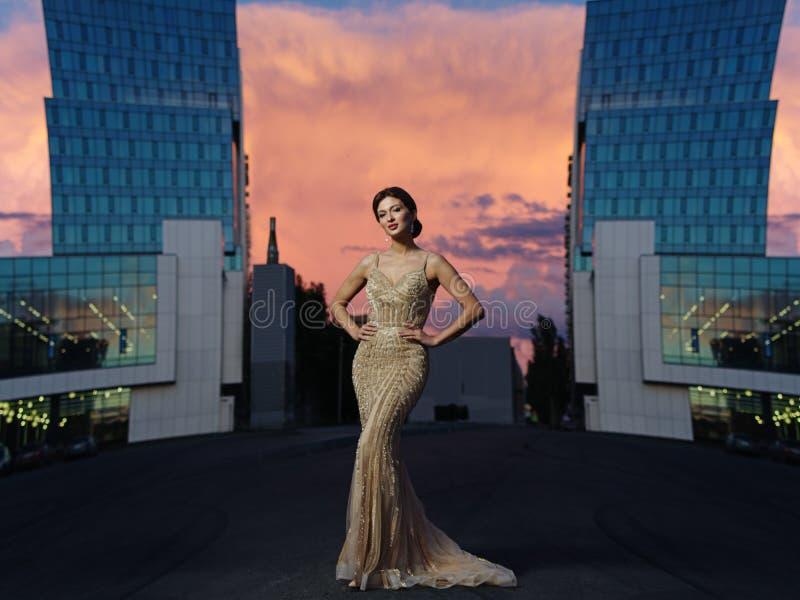 Mulher elegante espertamente vestida bonita nova com composição e penteado no vestido efervescente de nivelamento expressivo fotografia de stock royalty free