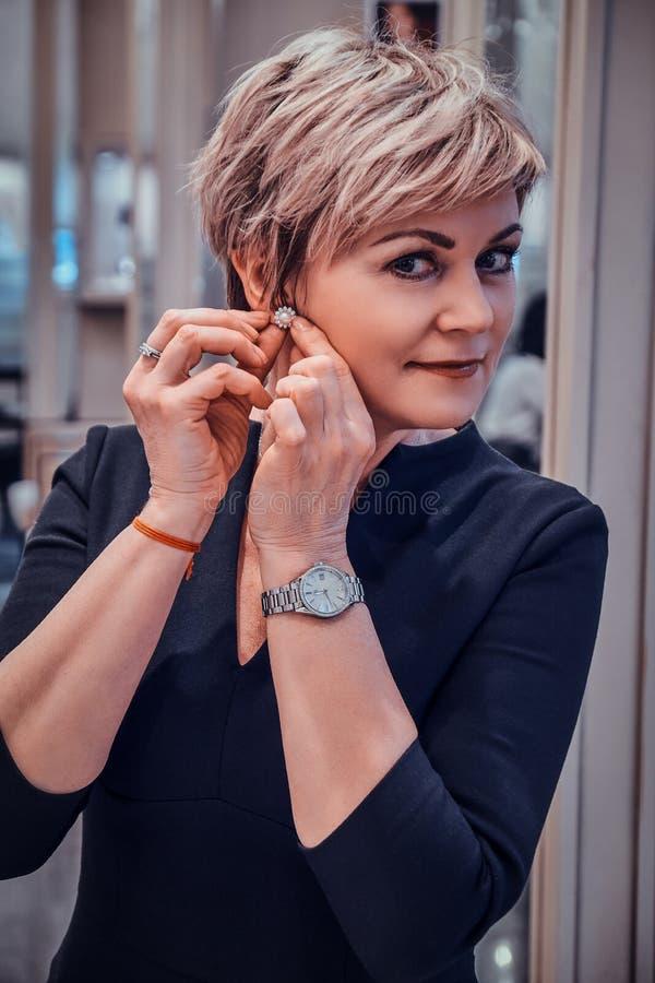 A mulher elegante est? tentando brincos novos da p?rola fotos de stock royalty free