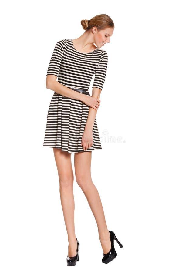 Mulher elegante magro nova no vestido com os pés longos que olham para baixo nas sapatas, isoladas no fundo branco Menina de sorr fotos de stock