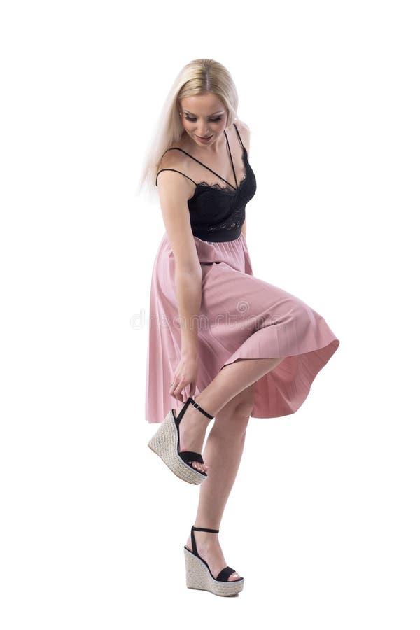Mulher elegante na saia da cor dos salmões que ajusta a correia da sapata da sandália da plataforma fotografia de stock