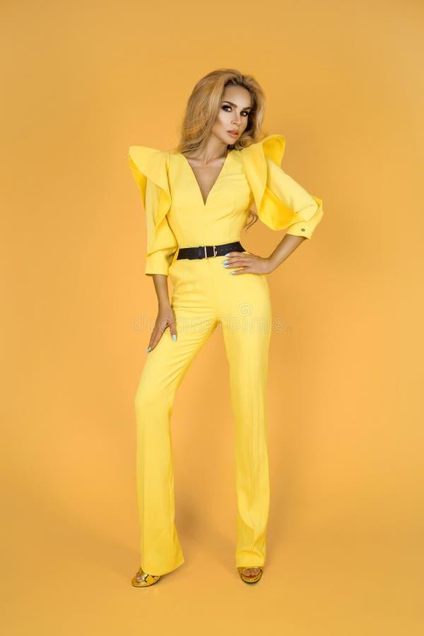 Mulher elegante no fato-macaco, em sapatas e em acessórios amarelos agradáveis Foto do verão da mola da forma - imagem foto de stock royalty free