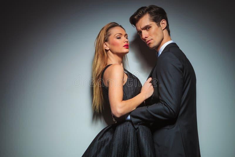 Mulher elegante no revestimento do homem puxando preto foto de stock royalty free