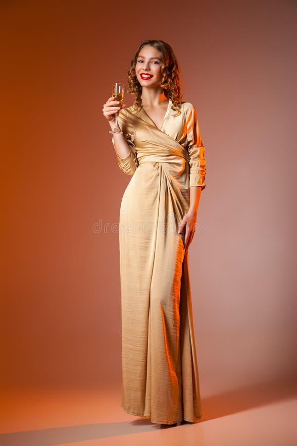 Mulher elegante no vestido dourado com copo de vinho foto de stock royalty free