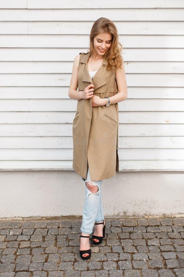 Mulher elegante nova em uma veste bege em um t-shirt branco em calças de brim rasgadas azuis à moda em sandálias pretas com uma b imagens de stock royalty free