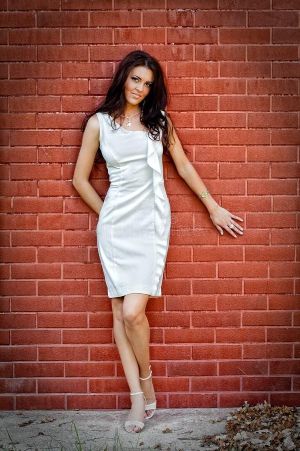 Mulher elegante nova 'sexy' na frente da parede de tijolo imagem de stock