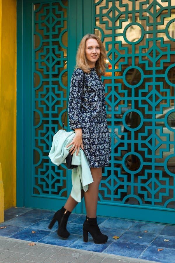 Mulher elegante perto da porta azul foto de stock royalty free
