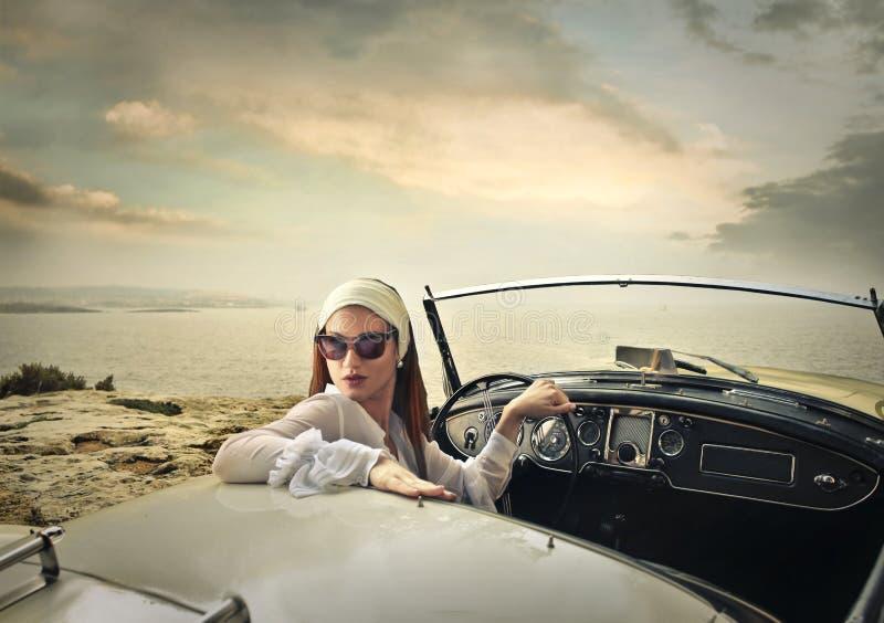Mulher elegante que conduz um carro foto de stock