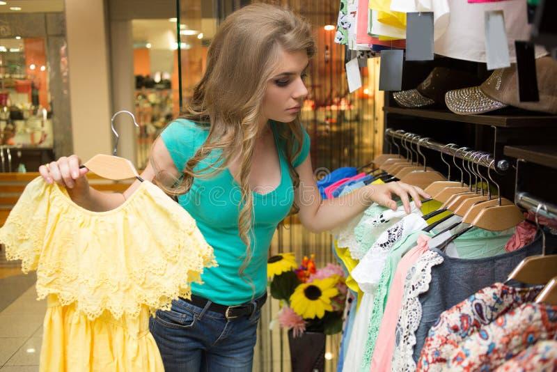 Mulher elegante que escolhe o vestido na loja fotografia de stock royalty free