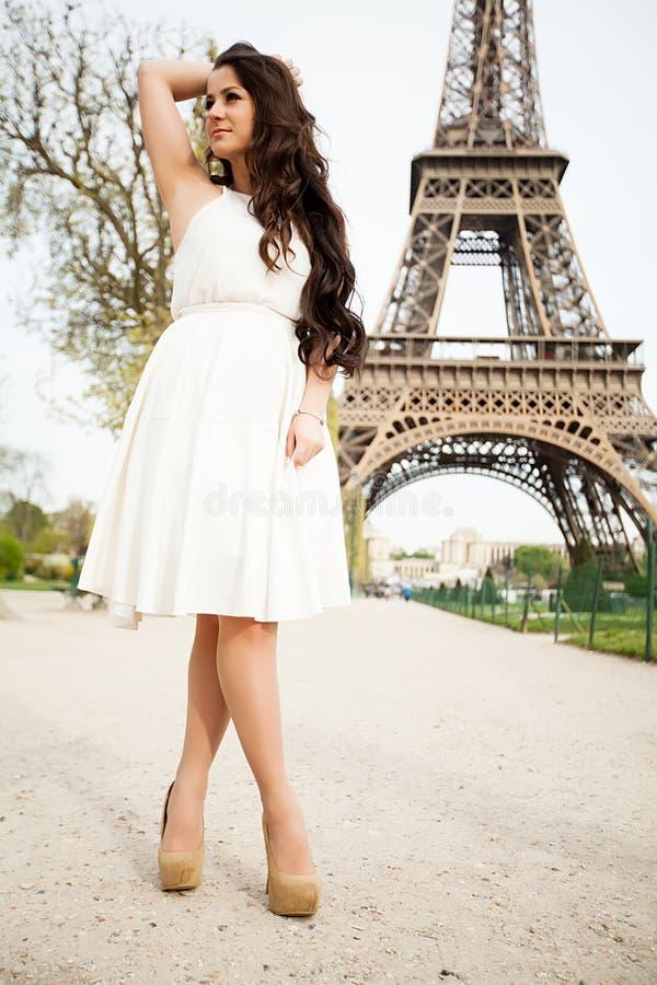 Mulher elegante que está em um parque com a torre Eiffel no fundo imagens de stock royalty free