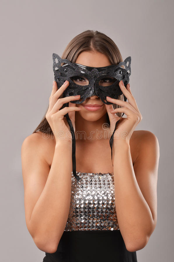 Mulher elegante que guarda uma máscara do disfarce foto de stock