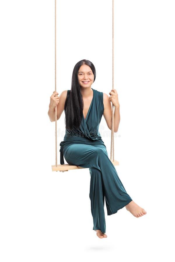 Mulher elegante que senta-se em um balanço imagem de stock