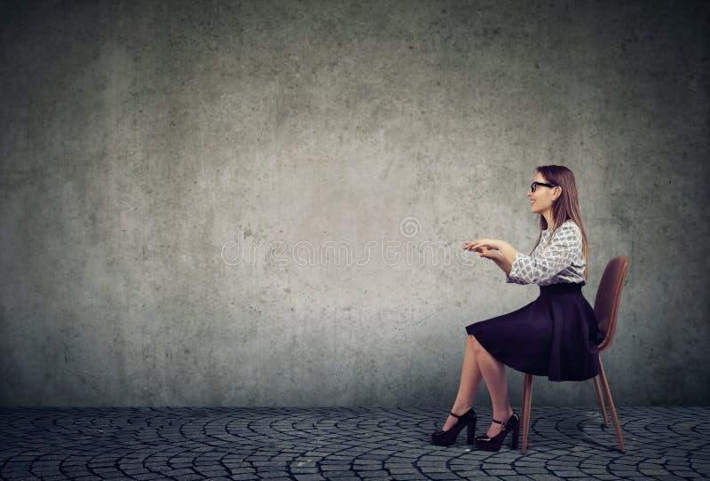 Mulher elegante que senta-se na tabela invisível que finge datilografar no computador imagem de stock royalty free