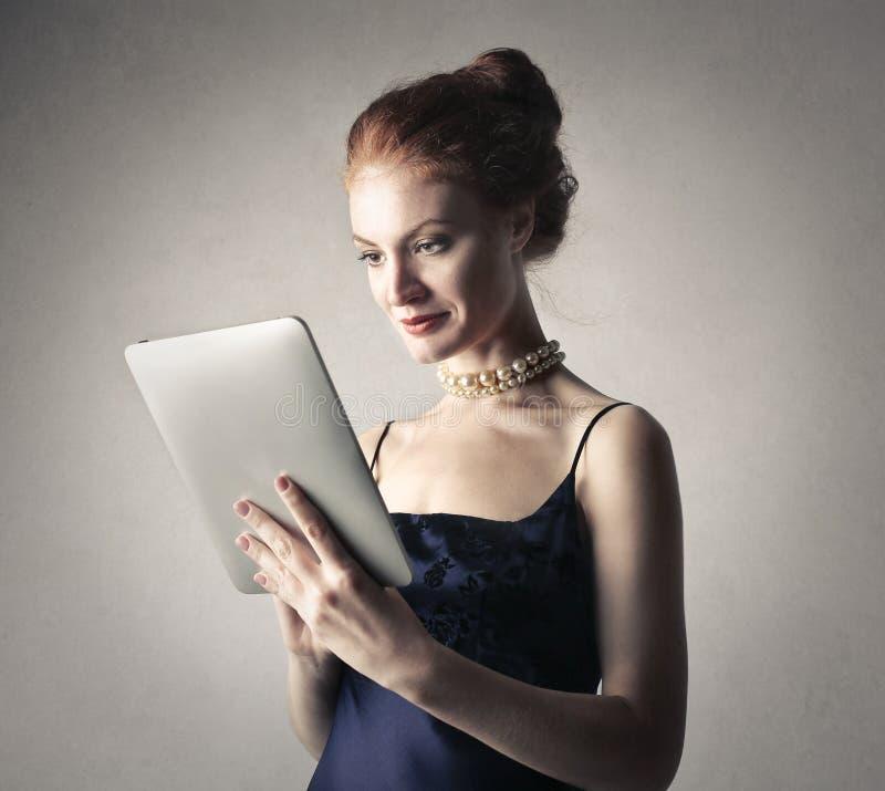 Mulher elegante que usa uma tabuleta foto de stock royalty free