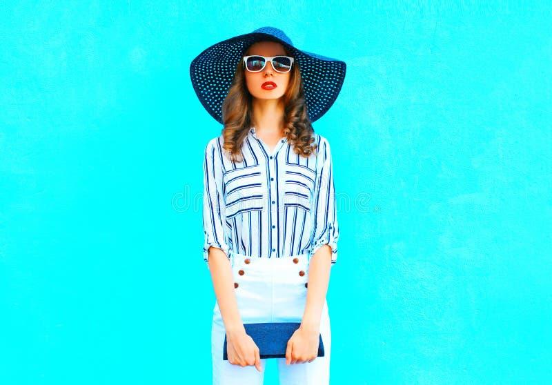Mulher elegante que veste um chapéu de palha, calças brancas com uma bolsa fotografia de stock