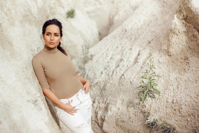 A mulher elegante segura que inclina-se na pedra, vestindo na roupa à moda, levanta na natureza, isolada fora do fundo fotografia de stock royalty free