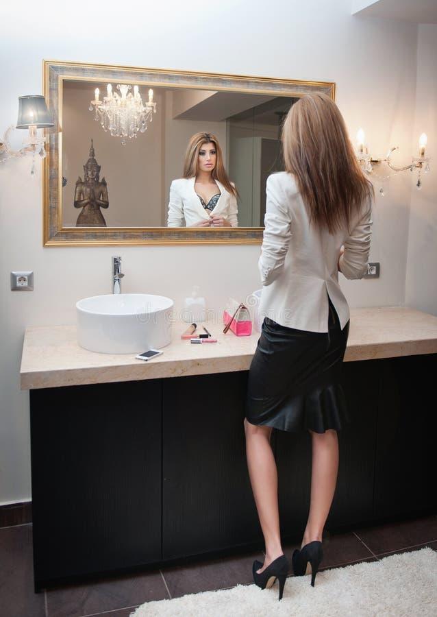 Mulher elegante sensual no equipamento do escritório que olha em um grande espelho. Revestimento branco vestindo da jovem mulher l foto de stock