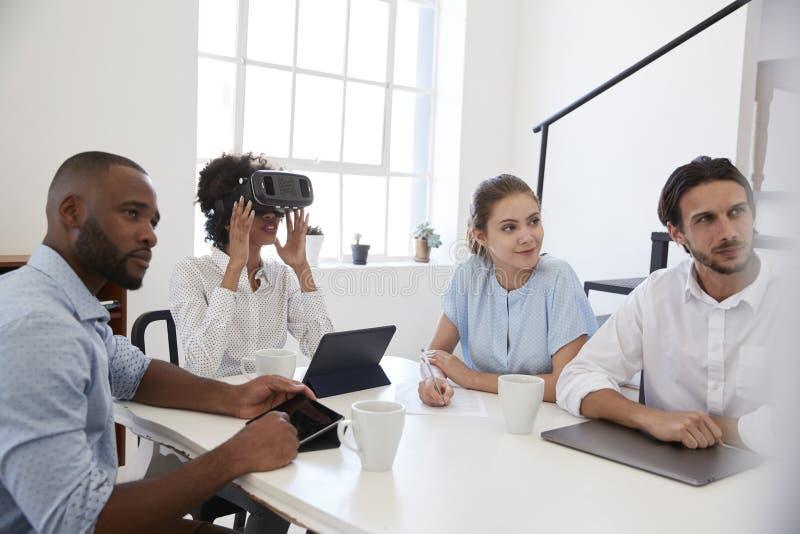Mulher em óculos de proteção de VR em uma mesa com colegas em um escritório fotos de stock royalty free