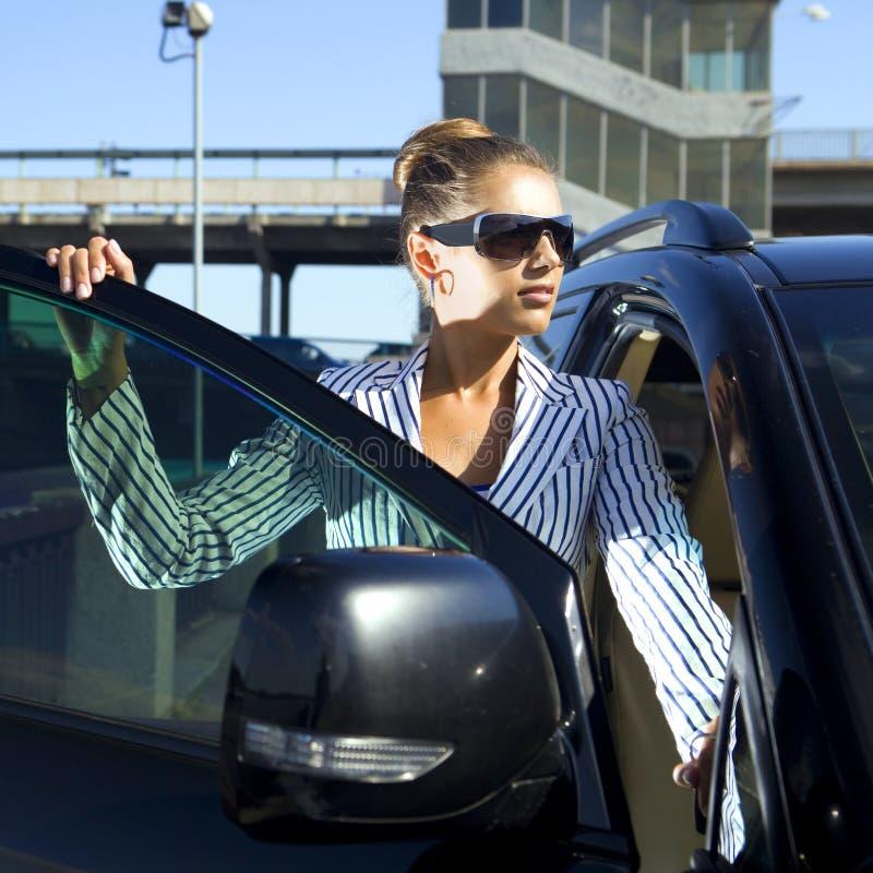 A mulher em óculos de sol pretos aproxima o carro imagem de stock royalty free