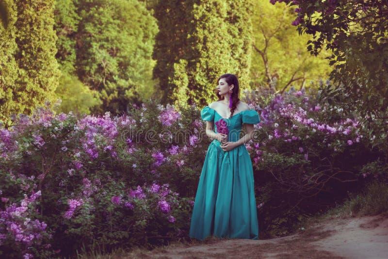 Mulher em arbustos lilás do lilás foto de stock royalty free