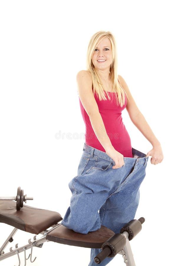 Mulher em calças grandes do banco de peso imagens de stock