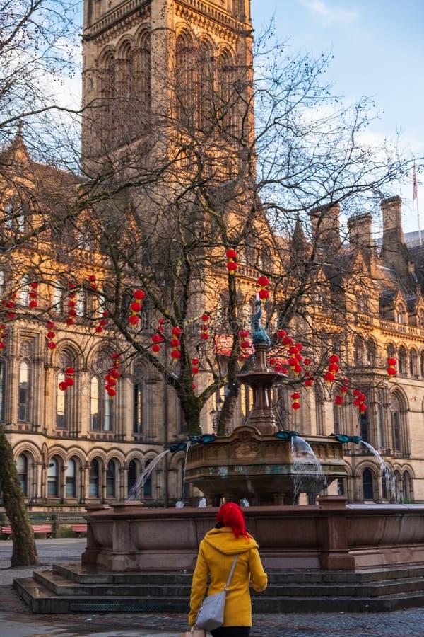 Mulher em caminhadas vermelhas do cabelo na frente da câmara municipal de Manchester decorada em lanternas chinesas vermelhas do  fotos de stock royalty free