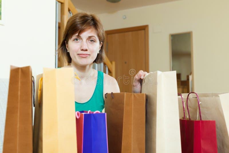 Mulher em casa com sacos de compra fotografia de stock