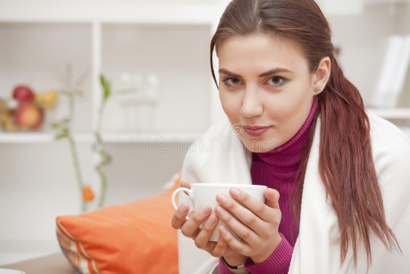 Mulher em casa que bebe o chá fotografia de stock royalty free
