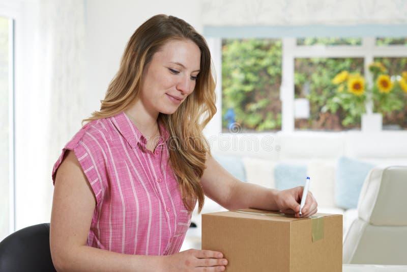 Mulher em casa que escreve o endereço no pacote imagem de stock