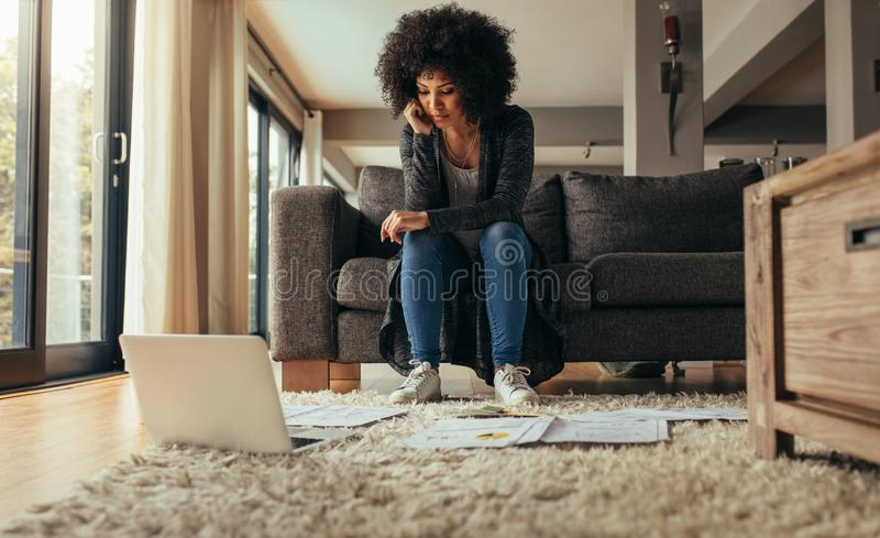 Mulher em casa que estuda papéis de negócio fotos de stock royalty free