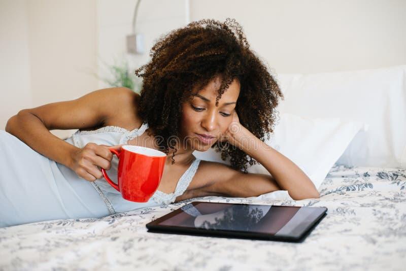 Mulher em casa que lê na tabuleta digital foto de stock